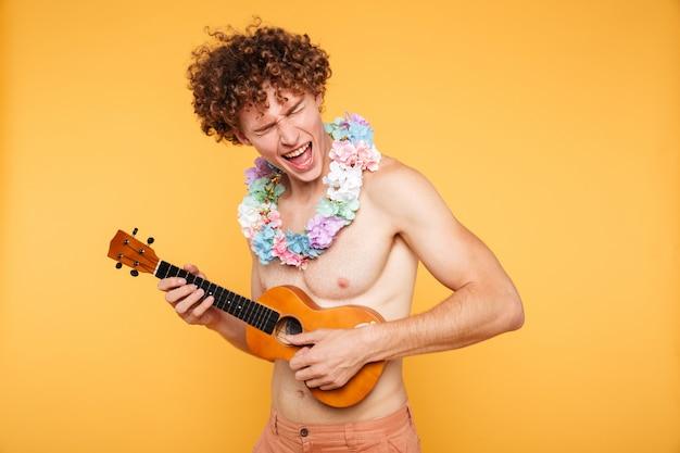 Attraktiver hemdloser mann in der sommerkleidung, die ukulele spielt