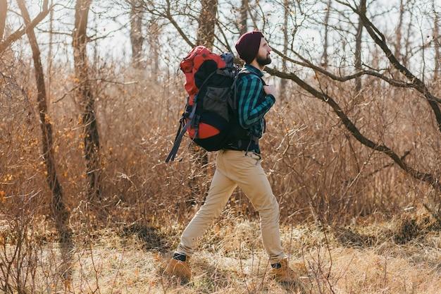 Attraktiver hipster-mann, der mit rucksack im herbstwald reist und kariertes hemd und hut trägt