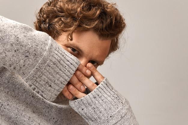 Attraktiver hipster-typ mit gewelltem ingwerhaar, der die finger über seinem gesicht mit durchdringendem gesichtsausdruck kreuzt, gekleidet in grauem pullover. copyspace zu ihrer information