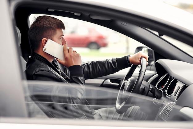 Attraktiver hübscher geschäftsmann, der mit telefon beim autofahren in der stadt spricht
