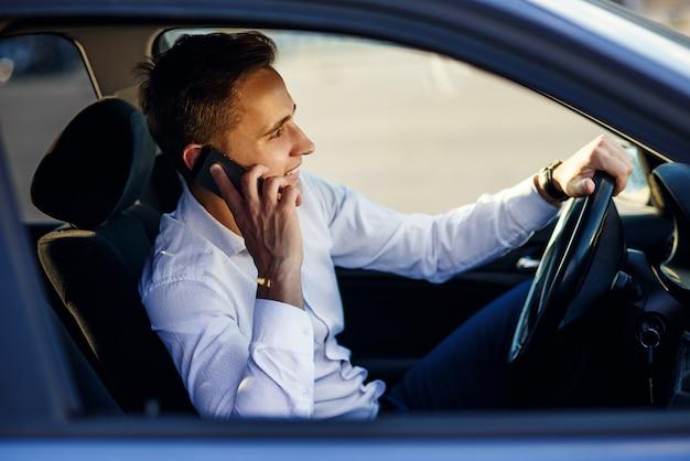 Attraktiver hübscher geschäftsmann, der mit telefon spricht, während er ein auto in der stadt fährt