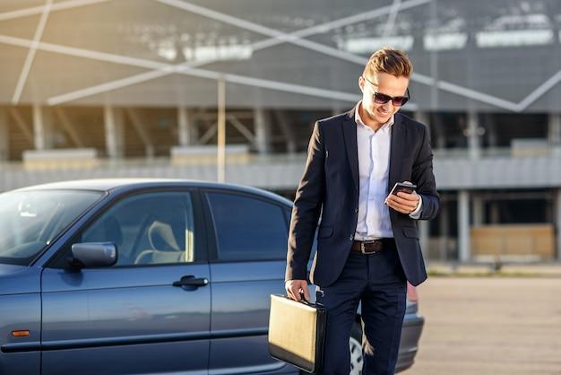 Attraktiver hübscher geschäftsmann mit diplomat und smartphone in den händen nahe dem auto