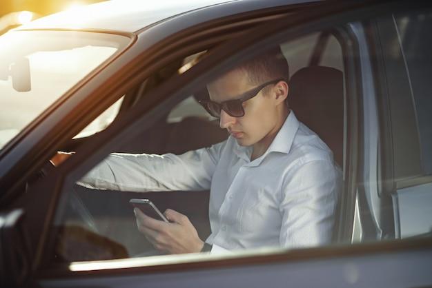 Attraktiver hübscher mann in der sonnenbrille, die smartphone in seinem auto verwendet