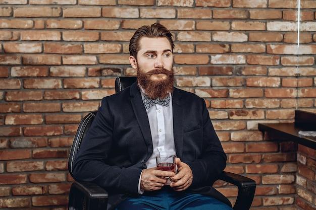 Attraktiver hübscher mann in einem anzug, der auf dem sitz sitzt und ein glas whisky und eine zigarre in seinen händen hält.