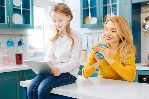 Attraktiver inhalt blonde, schlanke mutter, die lächelt und eine tasse tee und ihre tochter mit einer tablette hält, während sie auf dem tisch sitzt