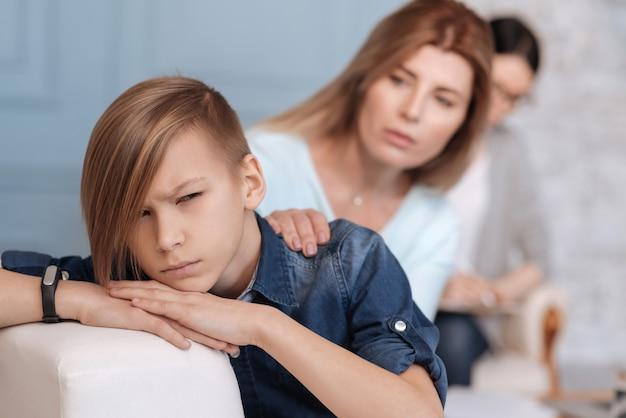 Attraktiver junge, der fitnessarmband auf der rechten hand trägt, die stilvollen haarschnitt hält hände auf weißem rücken des sofas hält