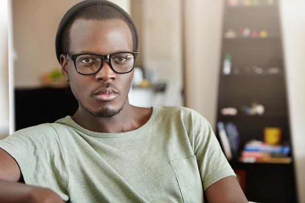 Attraktiver junger afroamerikaner, der trendige schwarze brille und hut trägt, die wochenendmorgen zu hause verbringen, im wohnzimmer sitzen, weltnachrichten im fernsehen sehen, ernsthaften blick haben