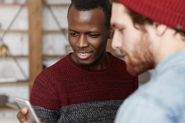Attraktiver junger afroamerikaner-mann im kuscheligen pullover, der handy hält