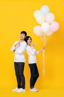 Attraktiver junger asiatischer liebhaber, der bunte ballons hält