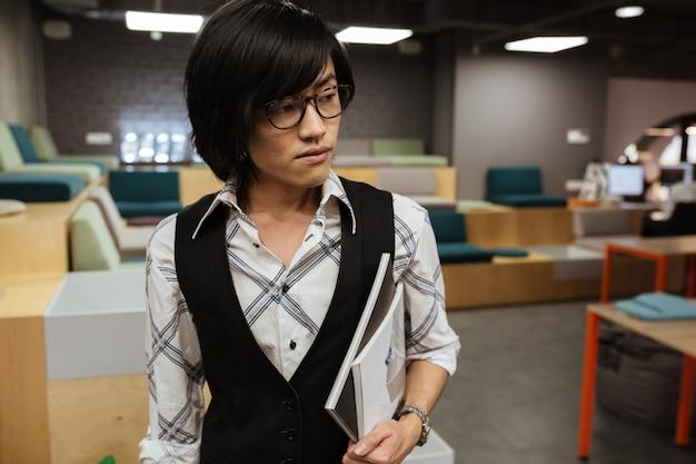 Attraktiver junger asiatischer mann, der brille trägt. coworking-konzept.