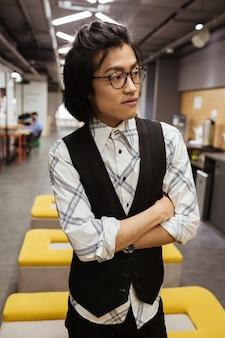 Attraktiver junger asiatischer mann, der brillen trägt, die beiseite schauen.