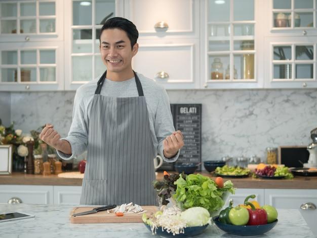 Attraktiver junger asiatischer mann, der ein schutzblech trägt und zu hause gesundes lebensmittel in der küche kocht.
