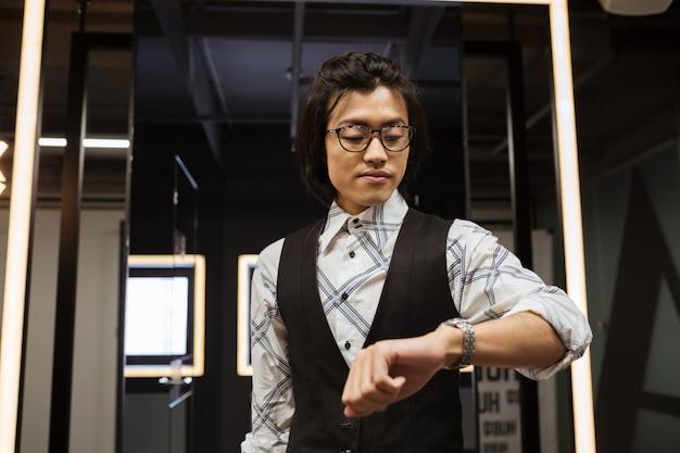 Attraktiver junger asiatischer mann, der uhr schaut. coworking-konzept.