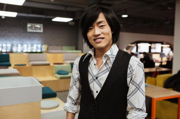 Attraktiver junger asiatischer mann gekleidet in jacke und hemd