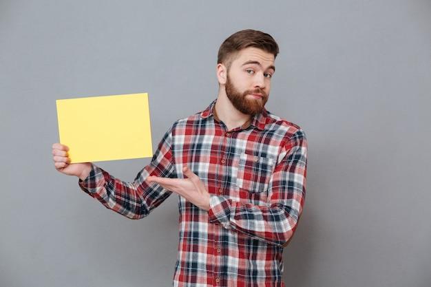 Attraktiver junger bärtiger mann, der leeres papier hält