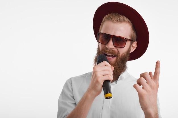 Attraktiver junger bärtiger schausteller, der stilvolle sonnenbrille und hut hält, mikrofon hält und vorderfinger hebt, während beliebte sängerleistung ankündigt