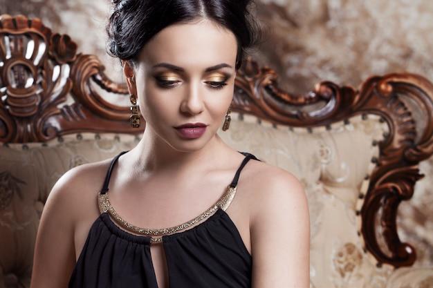 Attraktiver junger brunette, der auf schönem sofa, porträtnahaufnahme, goldaugenschminke sitzt
