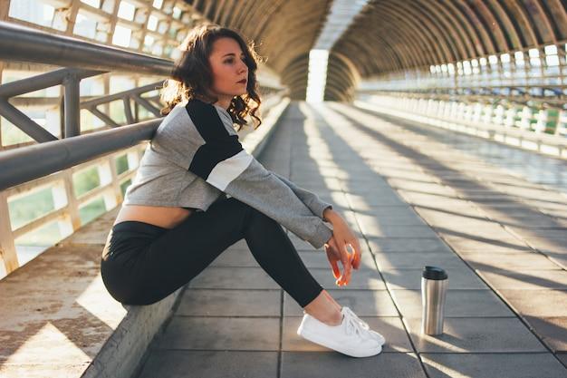 Attraktiver junger brunettefrauen-straßentänzerturner, der mit thermoschale auf brücke sitzt und stillsteht