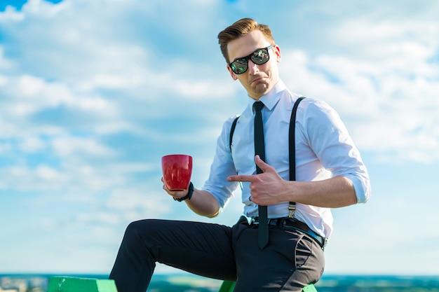 Attraktiver junger busunessman im weißen hemd, in der bindung, in den klammern und in der sonnenbrille mit roter schale
