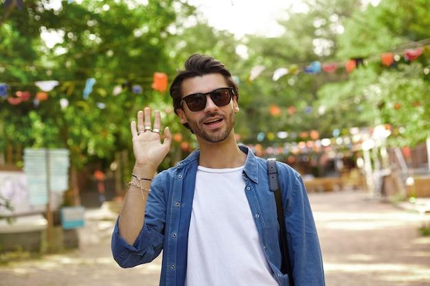 Attraktiver junger dunkelhaariger mann, der durch stadtgarten geht und hand in der willkommensgeste hebt, freizeitkleidung und sonnenbrille tragend