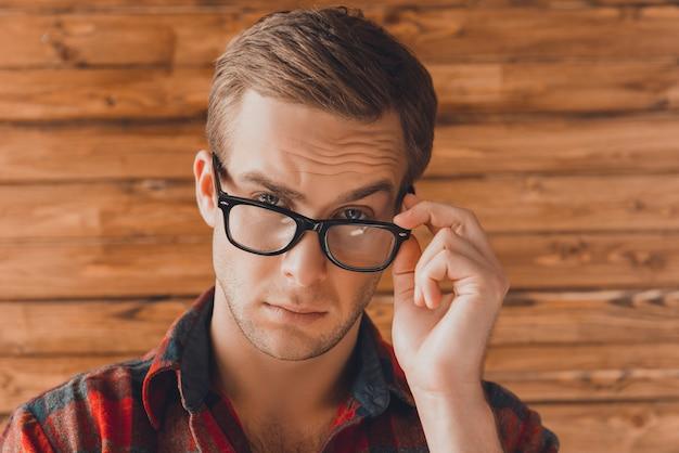 Attraktiver junger ernster mann, der seine brille berührt