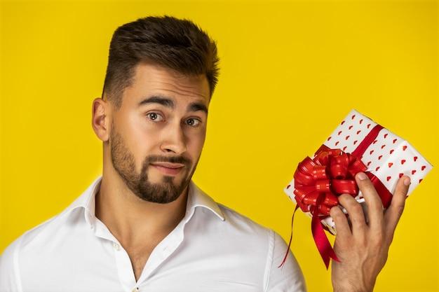 Attraktiver junger europäischer kerl im weißen hemd hält ein geschenk