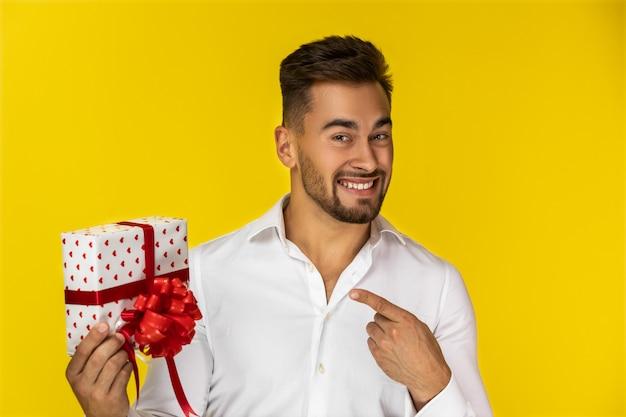 Attraktiver junger europäischer kerl im weißen hemd zeigt ein verpacktes geschenk