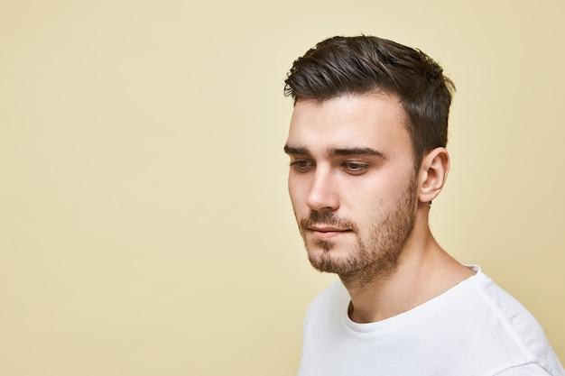 Attraktiver junger europäischer mann mit borsten, die mit schüchternem lächeln herabblicken, das im weißen t-shirt gegen leere wand mit kopienraum für ihre werbeinformationen aufwirft