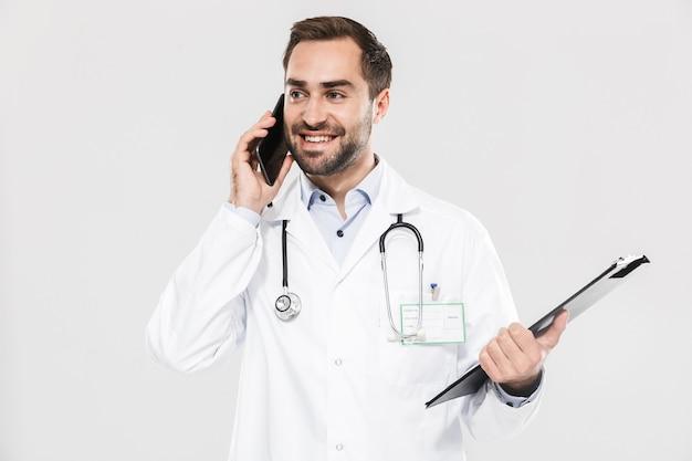 Attraktiver junger fröhlicher männlicher arzt, der eine unifrom trägt, die isoliert über der weißen wand steht und sich beim telefonieren notizen macht