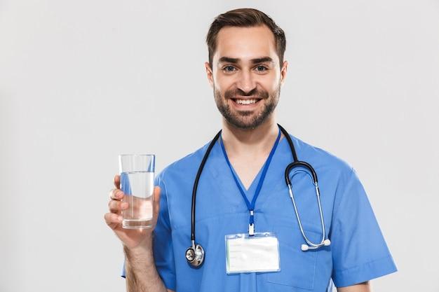 Attraktiver junger fröhlicher männlicher arzt, der unifrom stehend über weißer wand trägt und ein glas wasser zeigt