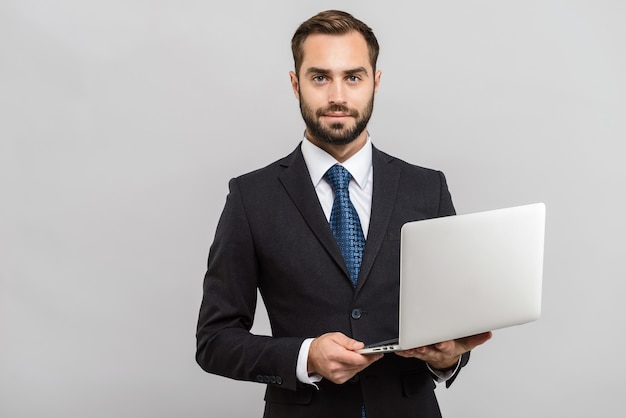 Attraktiver junger geschäftsmann, der anzug trägt, der isoliert über grauer wand steht, mit laptop-computer