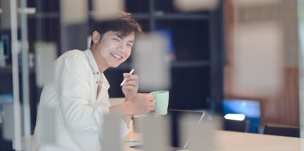 Attraktiver junger geschäftsmann, der eine kaffeepause hat