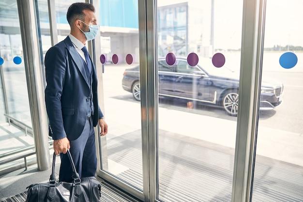 Attraktiver junger geschäftsmann, der eine medizinische maske trägt, während er mit seinem gepäck in der eingangshalle eines flughafens steht und nach draußen schaut