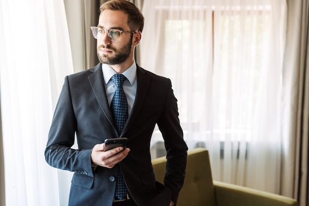 Attraktiver junger geschäftsmann im anzug, der im hotelzimmer steht und handy benutzt