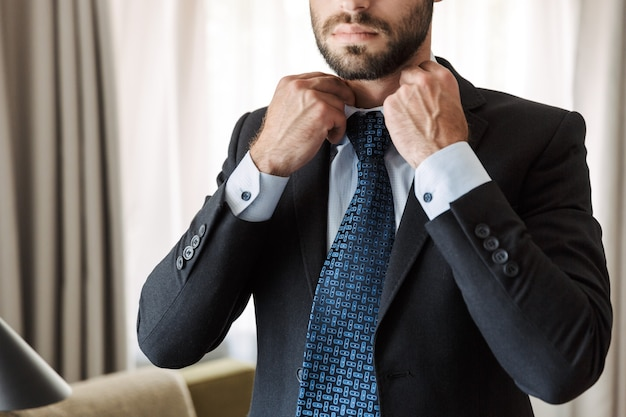 Attraktiver junger geschäftsmann im anzug, der im hotelzimmer steht und sich verkleidet