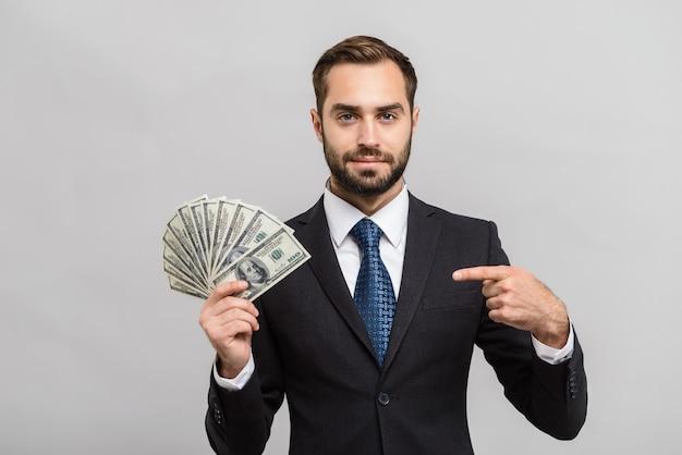 Attraktiver junger geschäftsmann im anzug, der isoliert über grauer wand steht, geldscheine zeigt und mit dem finger zeigt