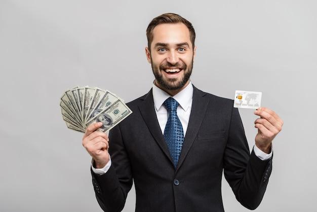 Attraktiver junger geschäftsmann im anzug, der isoliert über grauer wand steht und geldbanknoten und plastikkreditkarte zeigt