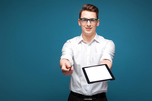 Attraktiver junger geschäftsmann in der kostspieligen uhr, in den schwarzen gläsern und im weißen hemd halten leere tablette und stift