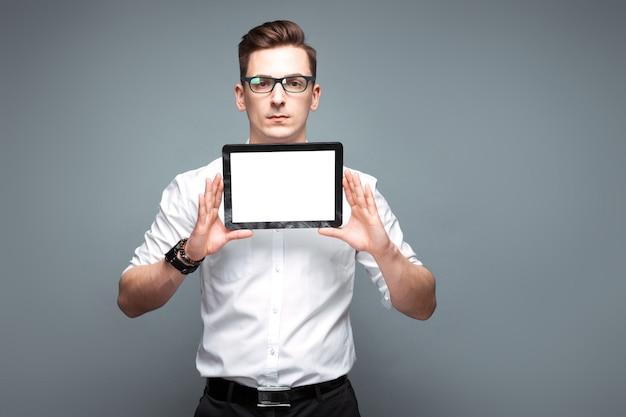 Attraktiver junger geschäftsmann in der kostspieligen uhr, in den schwarzen gläsern und im weißen hemd halten leere tablette
