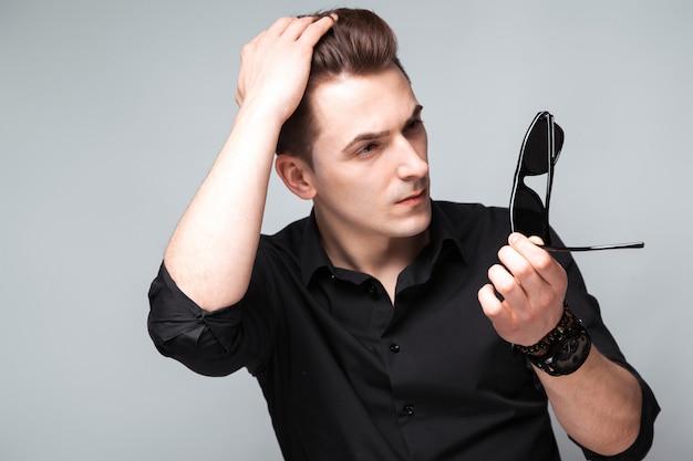 Attraktiver junger geschäftsmann in der kostspieligen uhr, in der sonnenbrille und im schwarzen hemd