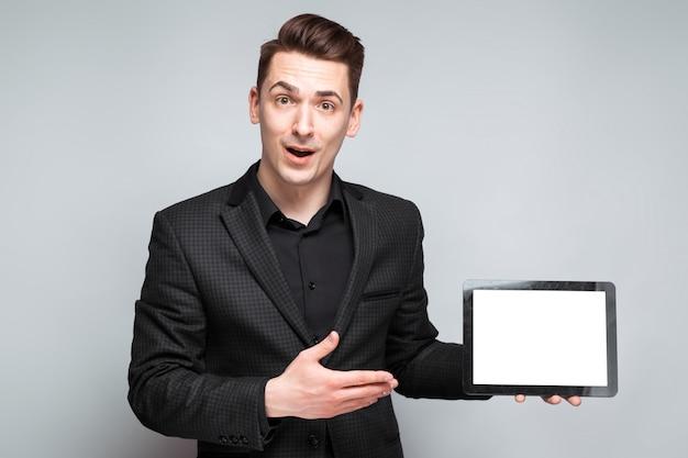 Attraktiver junger geschäftsmann in der schwarzen jacke, in der kostspieligen uhr und im schwarzen hemd halten leere tablette