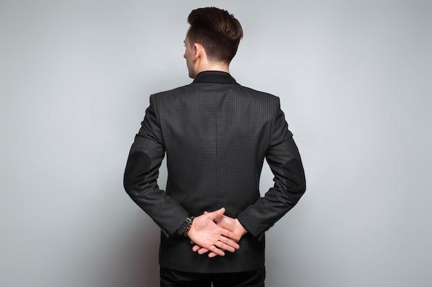 Attraktiver junger geschäftsmann in der schwarzen jacke, in der kostspieligen uhr und im schwarzen hemd