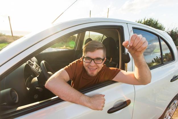 Attraktiver junger glücklicher mann, der seine neuen autoschlüssel zeigt und lacht.