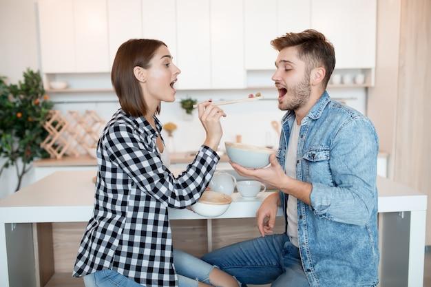 Attraktiver junger glücklicher mann und frau in der küche, frühstückend, paar zusammen am morgen, lächelnd