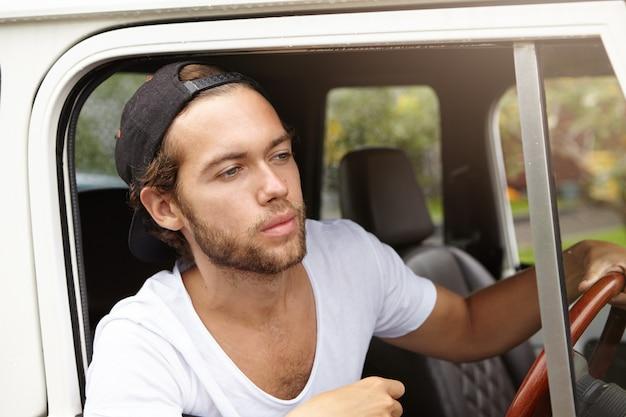 Attraktiver junger kaukasischer hipster-mann mit bart, der schwarze baseballkappe und weißes v-ausschnitthemd trägt, das weißes sport utility vehicle entlang der landstraße fährt