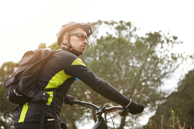 Attraktiver junger kaukasischer radfahrer in der stilvollen schwarzen und gelben fahrradkleidung, die sich umschaut