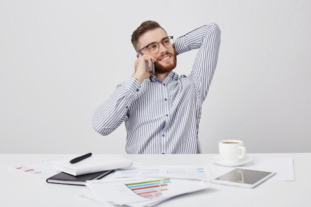 Attraktiver junger männlicher arbeiter mit ansprechendem aussehen hat kaffeepause, fühlt sich entspannt