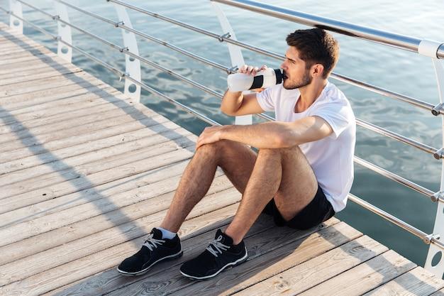 Attraktiver junger männlicher athlet, der auf pier sitzt und wasser trinkt