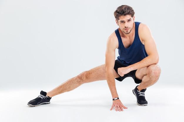 Attraktiver junger männlicher athlet, der seine beine über weißem hintergrund ausdehnt