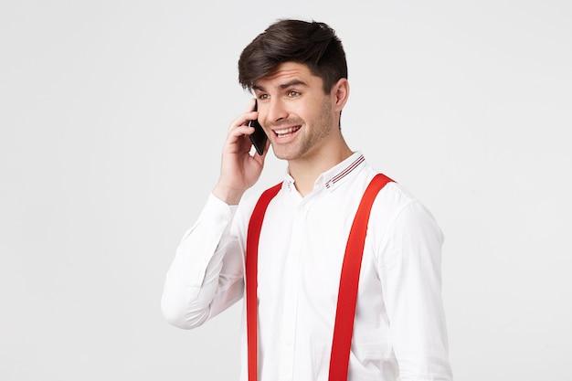 Attraktiver junger mann, der am telefon spricht, sieht froh glücklich aus, lächelt und fühlt sich von positiven emotionen überwältigt